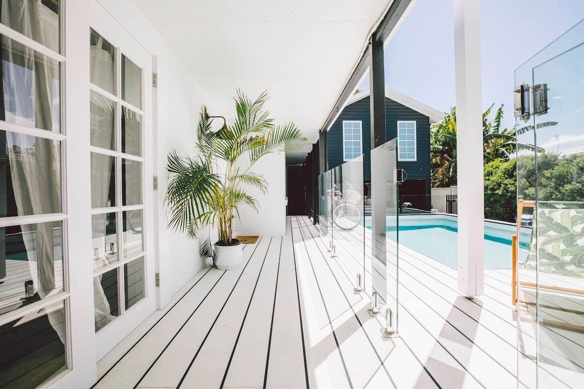 a white verandah area next to a pool