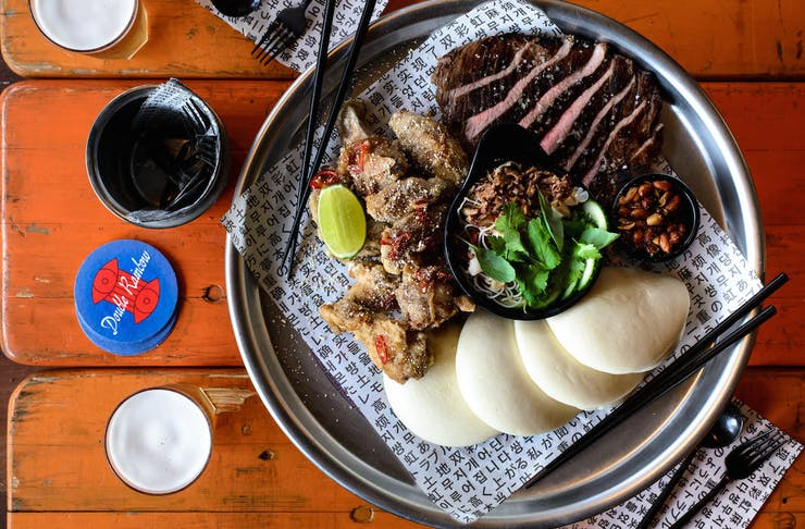 Grilled steak, lotus buns and chicken wings sit on a silver platter atop a wooden bench.
