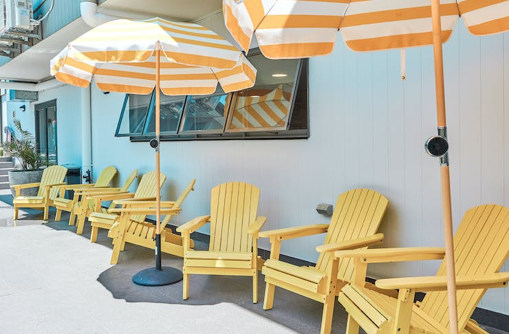 Bright yellow sun chairs sit underneath white and yellow striped umbrellas.