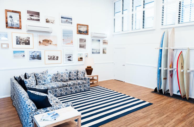 A blue and white L-shape couch sits underneath a gallery wall at a Byron Bay hostel. There is a rack of surfboards against the wall.