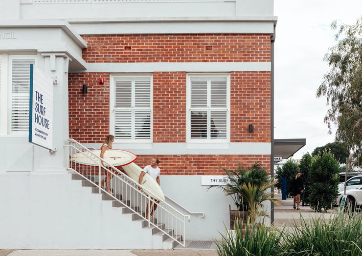 Two surfers walk down the stairs of The Surf House, a hostel in Byron Bay.