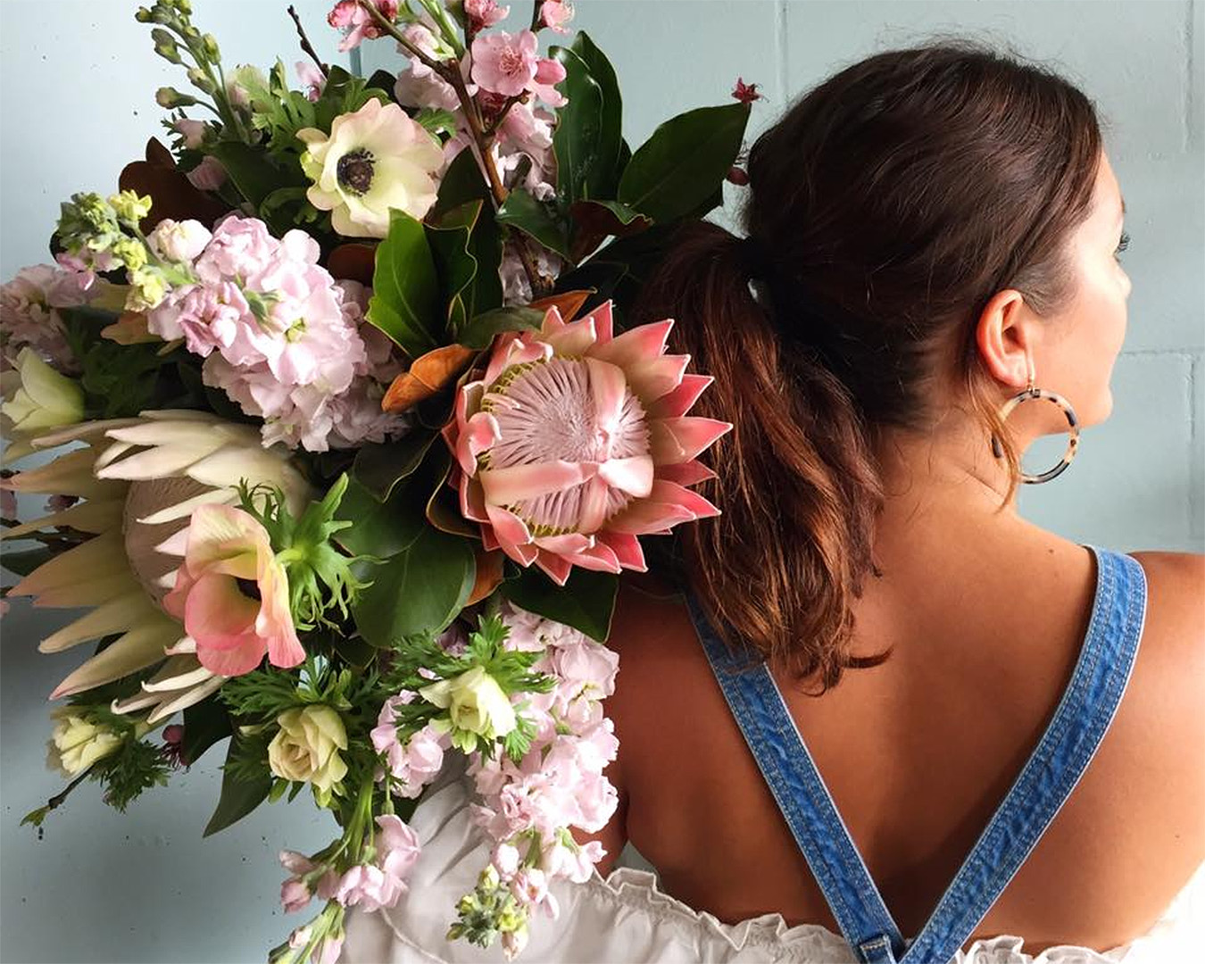 A girl holds a beautiful bouquet over her shoulder.
