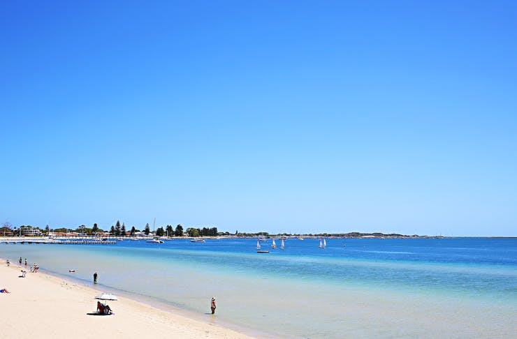 a stunning view of the beach with blue skies and white sand.