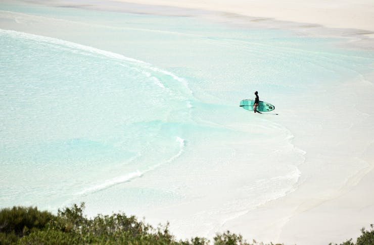 Person with surfboard walking from the sand into the ocean
