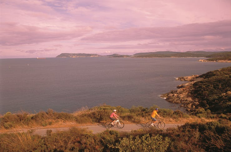 Two people ride their bikes down a dirt path set to a stunning pink sunset.