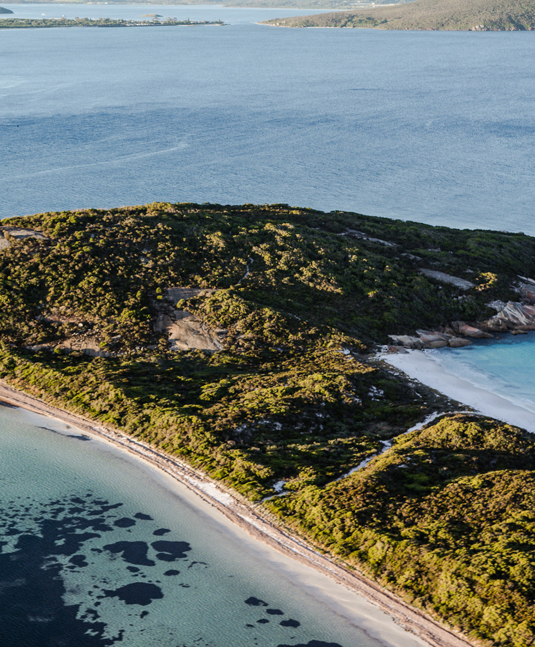 Lush bush intersects with clear blue waters in Albany, WA.