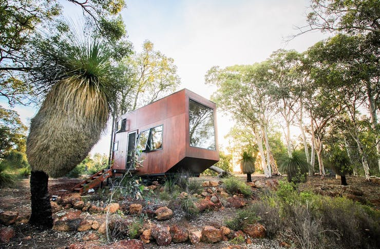 A tiny wooden cabin sits amongst the bush in the Chittering, Perth