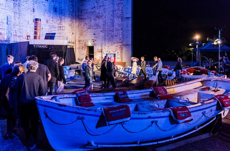 audience and cast standing near a life boat in a theatre