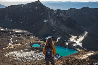 A walker looks out at a green lake on the Tongariro Crossing, Ruapehu