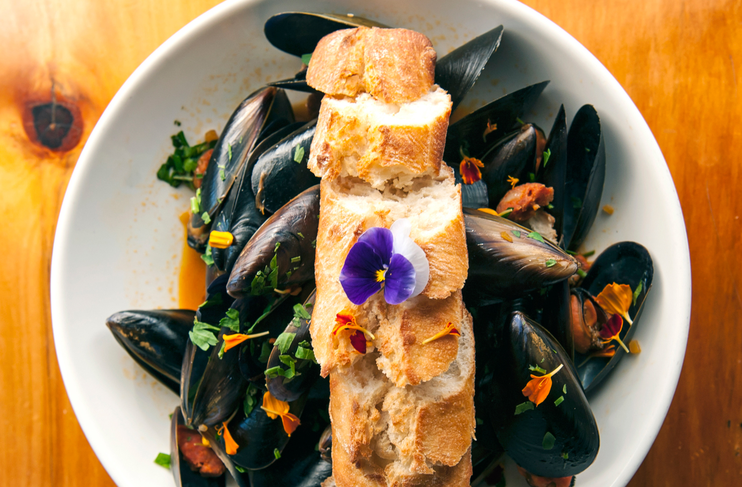 A delicious looking dish of mussels topped with a baguette from Mavis' Kitchen.