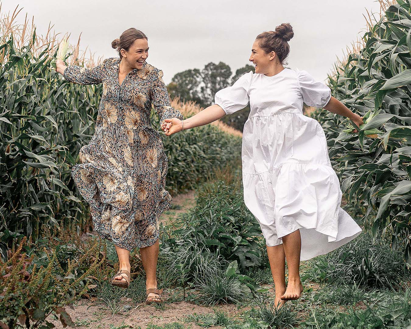 Margo And Rosa skip through a field together happy as clams.