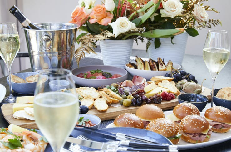 A spread of delicious food including sliders, an assortment of cheeses, fresh bread and champagne.
