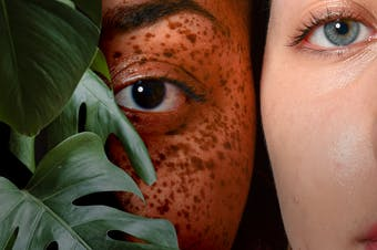 Very close up of two people, one has dark skin with freckles and one has light skin. A Monstera leaf is covering part of their faces.
