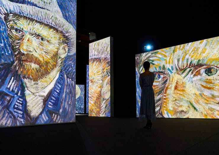 A person takes a picture of a huge Vincent Van Gogh self portrait projected onto a wall.