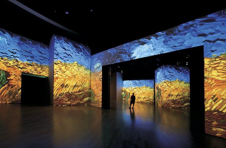 A person walks amongst a massive Van Gogh painting.