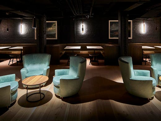 The dimly lit interior of Valhalla with suede cyan blue chairs and booth seating in the background