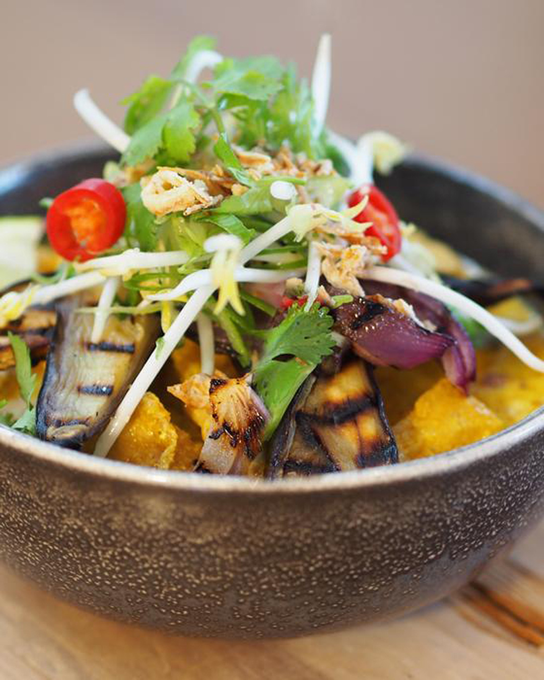 Delicious bowl of healthy looking food with greens and grilled aubergine.