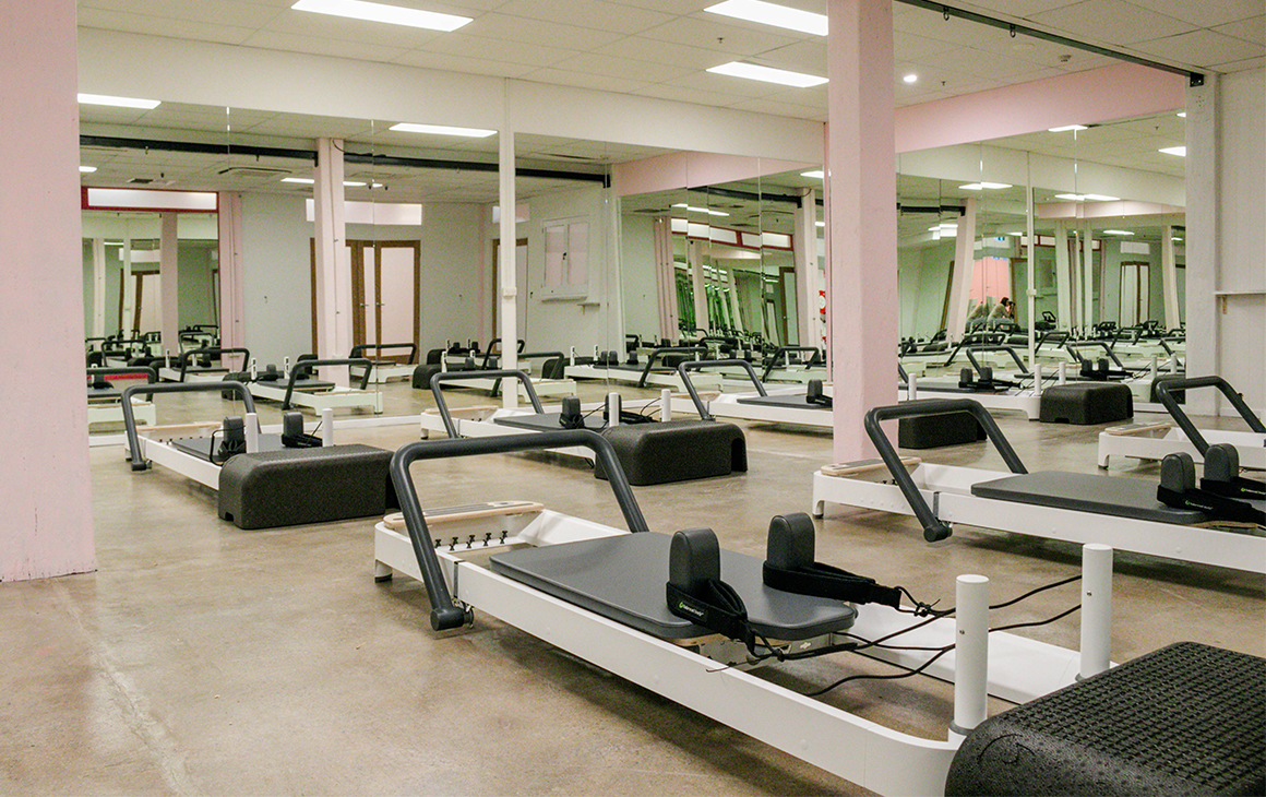 A mirror lined room filled with reformer beds.