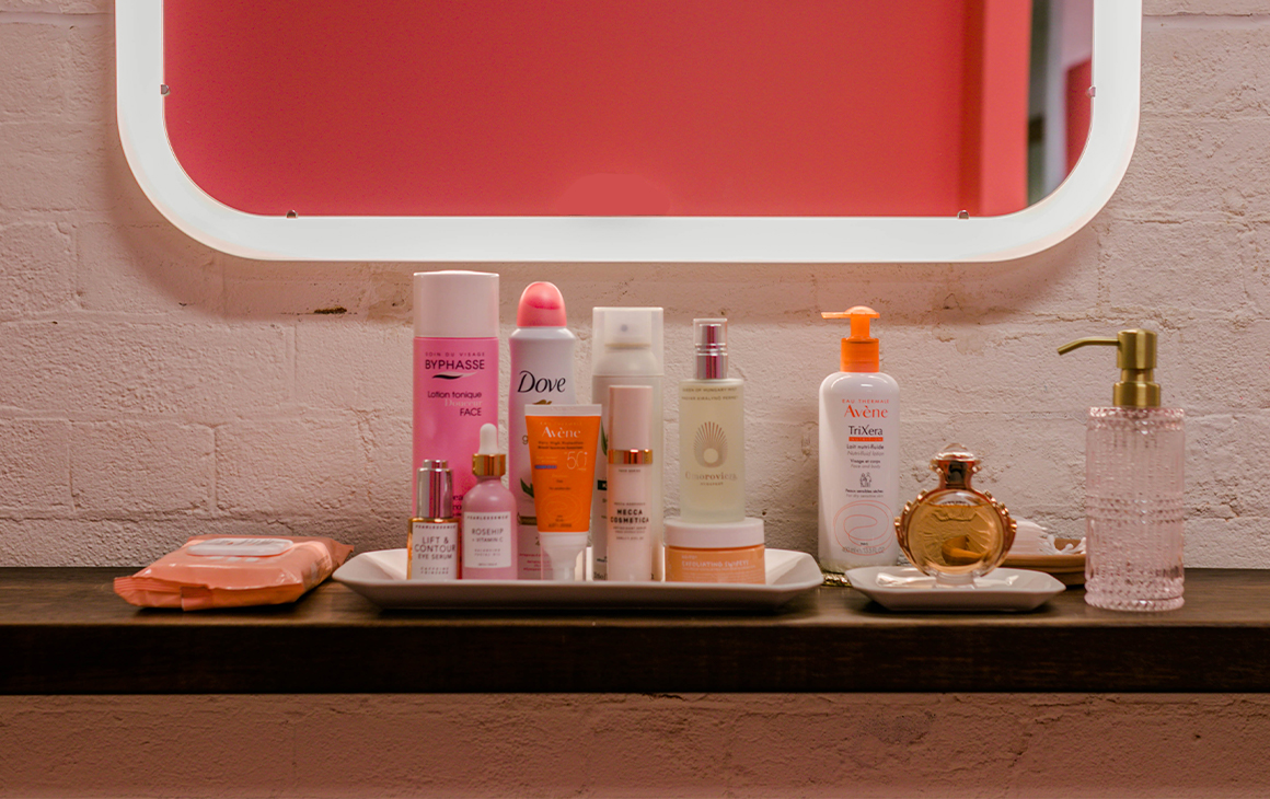 Beauty products arranged on a bench in front of a mirror