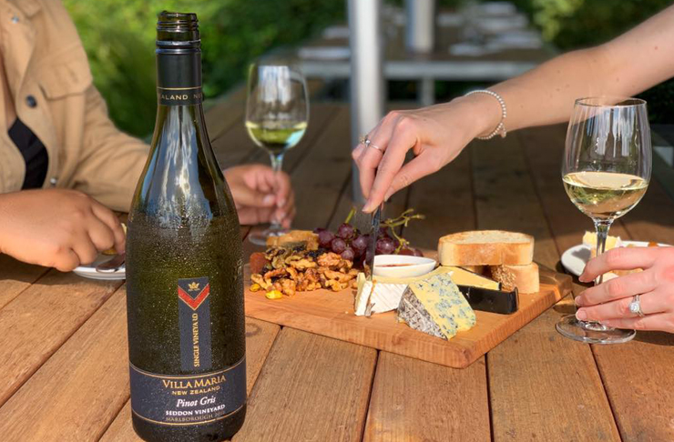 A bottle of Pinot Gris in front of a cheese platter