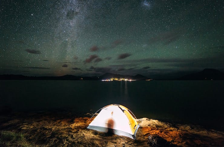 A small tent is set up beside a lake beneath a canopy of stars.