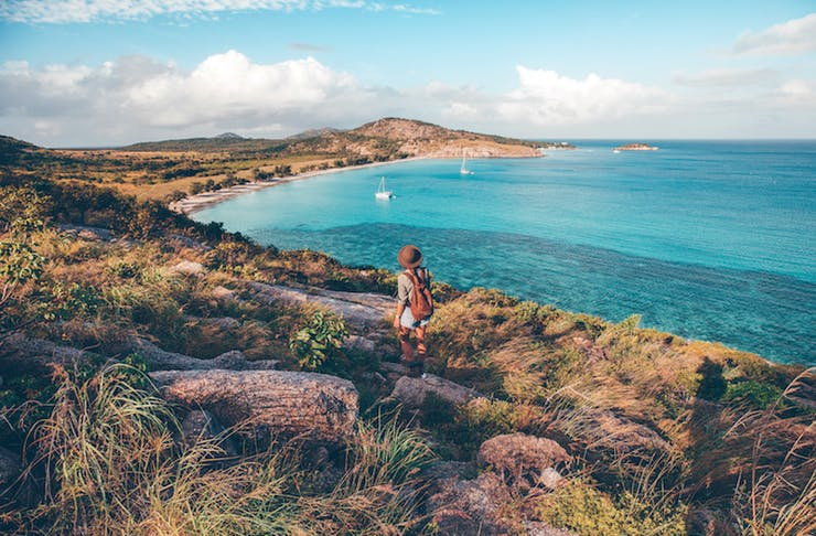A woman stands on a cliff overlooking a turquoise bay.