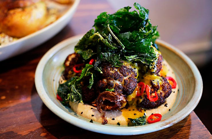 Whole roasted cauliflower topped with greens and chilli