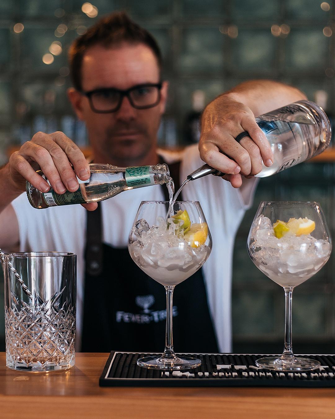 A bartender mixes drinks in an artful way.