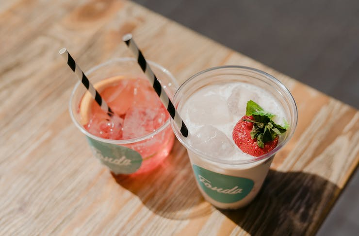 Two frozen cocktails each in a cup with a straw and garnished with a strawberry.