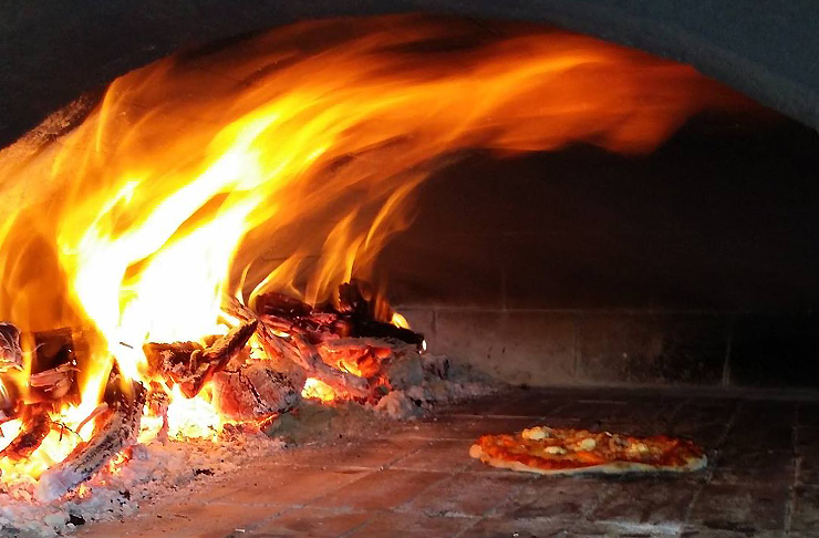 A pizza cooks next to big open flame in a wood fire pizza oven