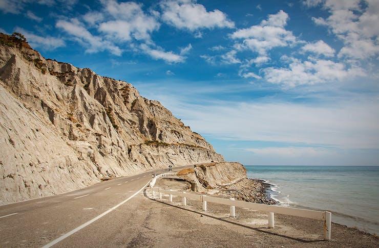 Road through eroded limestone coastal cliff at Palliser Bay, Wairarapa