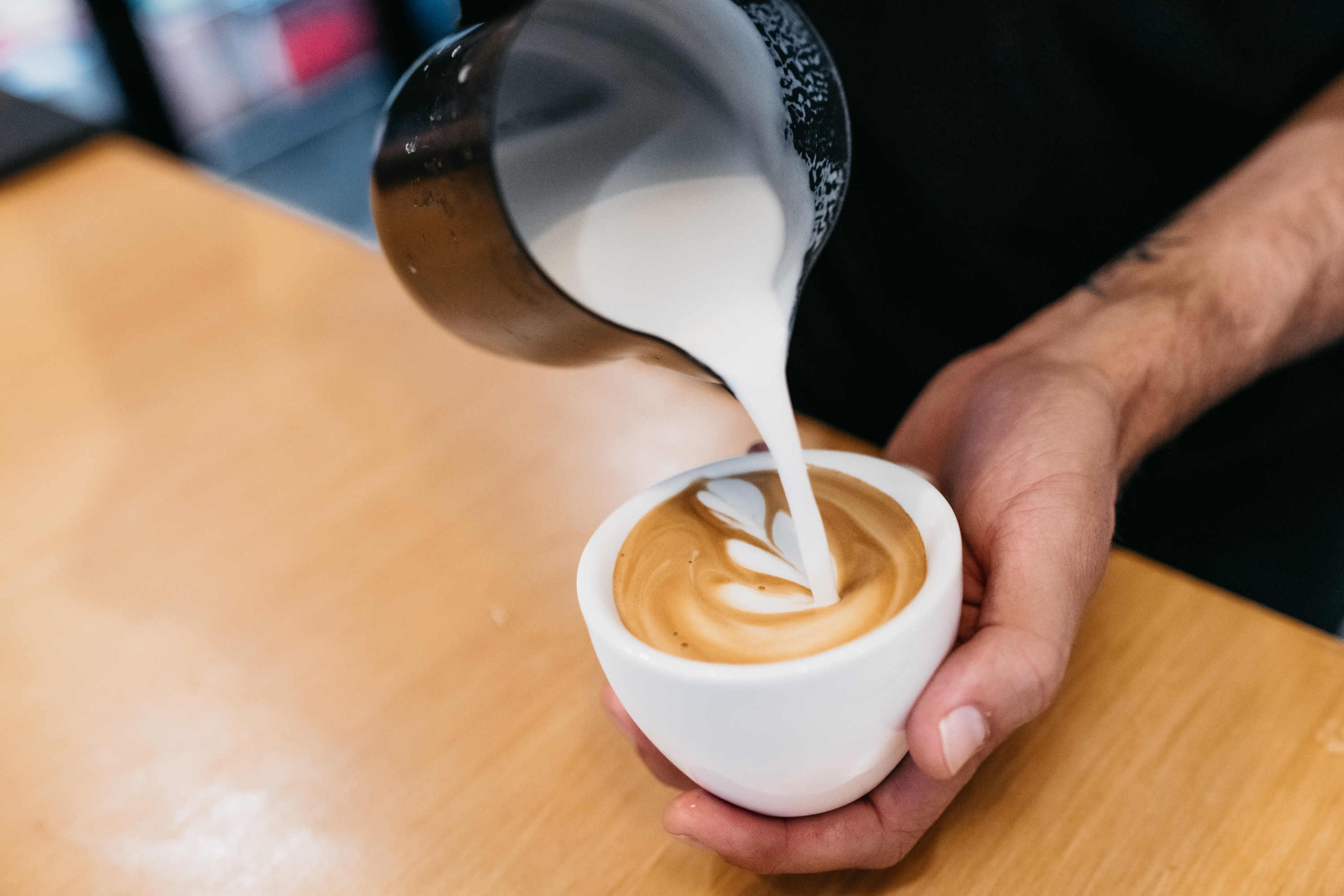 a close up shot of a person pouring coffee in a cup