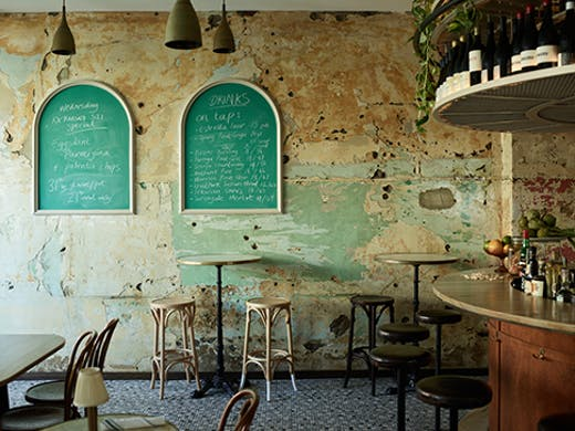 The inside of the bar with paint stripped walls, bar stools, and wine.