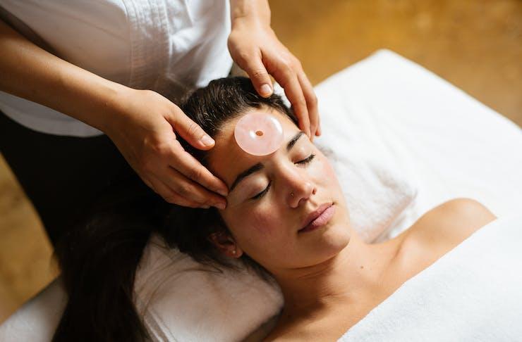 A lady gets a facial with a rose quartz stone