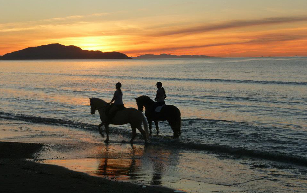 Two people ride horseback along Otaki beach at sunset.