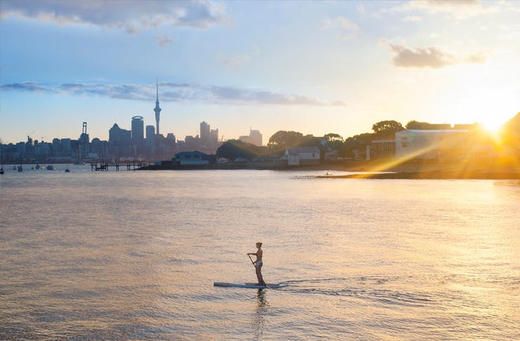 A person paddles across Auckland's Waitemata Harbour on a paddle board at sunrise with the city in the distance.