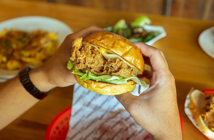 Someone holds a winner winner chicken burger in their hot little hands.