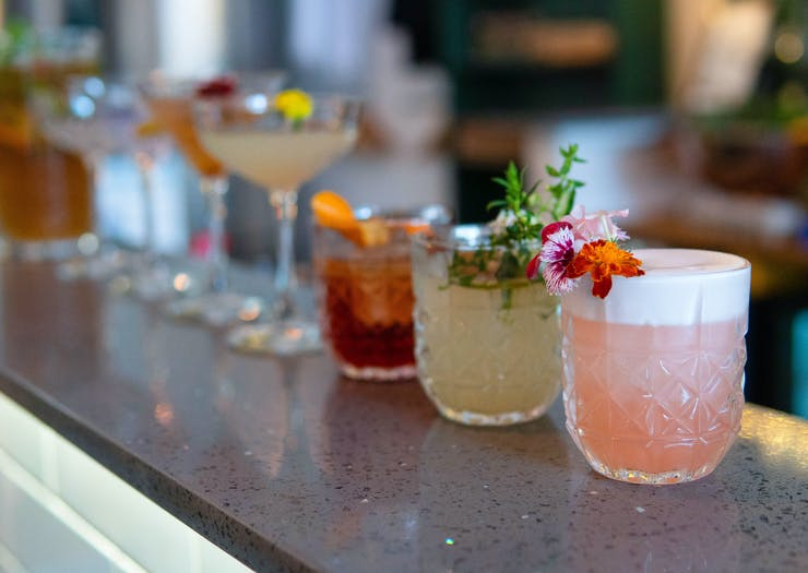 cocktails line up in a row at a bar