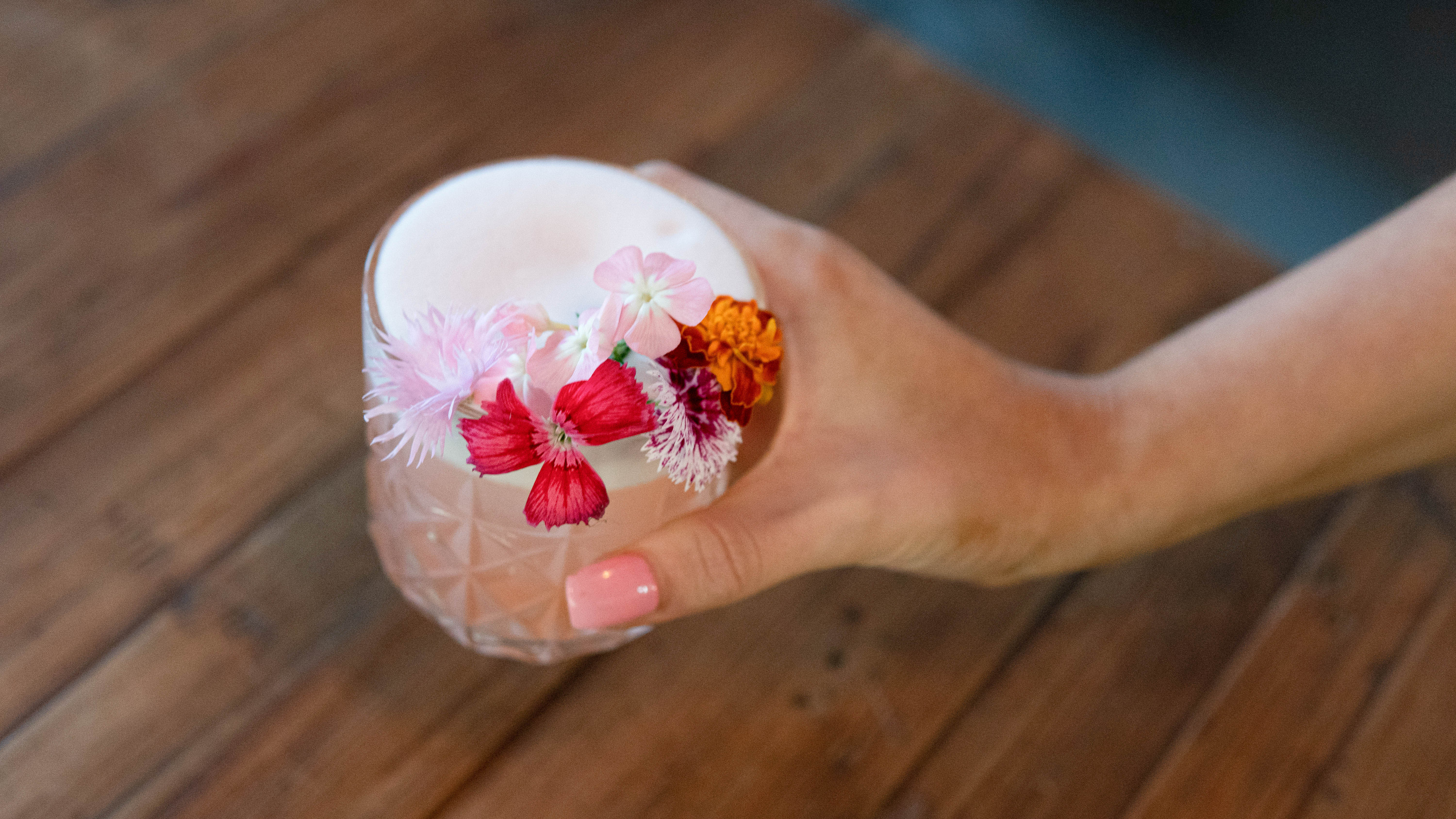 A hand holding a pink cocktail in a short glass, adorned with flowers
