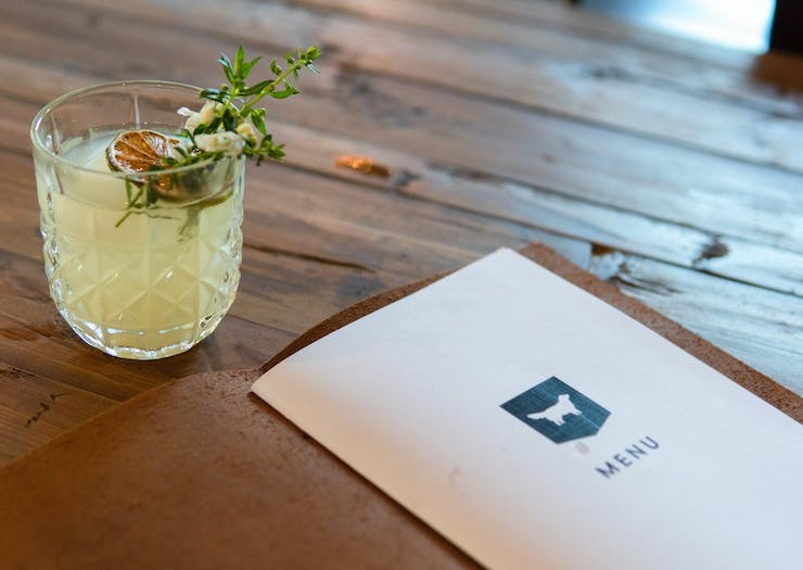 A cocktail and menu on a table.