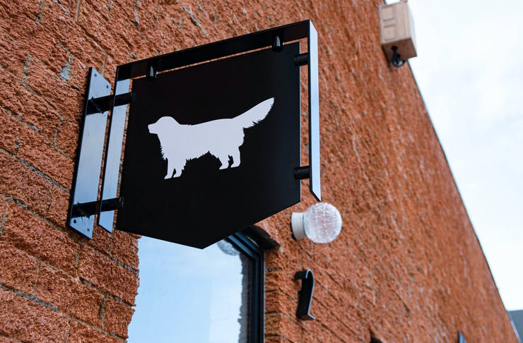 A sign with the outline of a dog on the outside of the brick building.