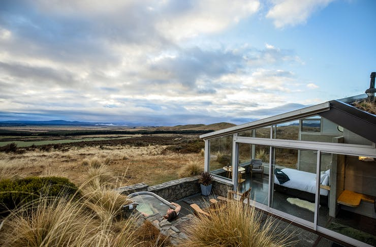 A person soaking in the outdoor hot tub at Skyscape accomodation looking out at views of Mackenzie Country
