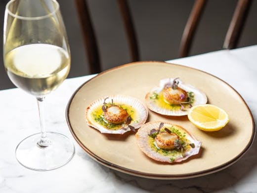 Glass of wine and a plate of scallops