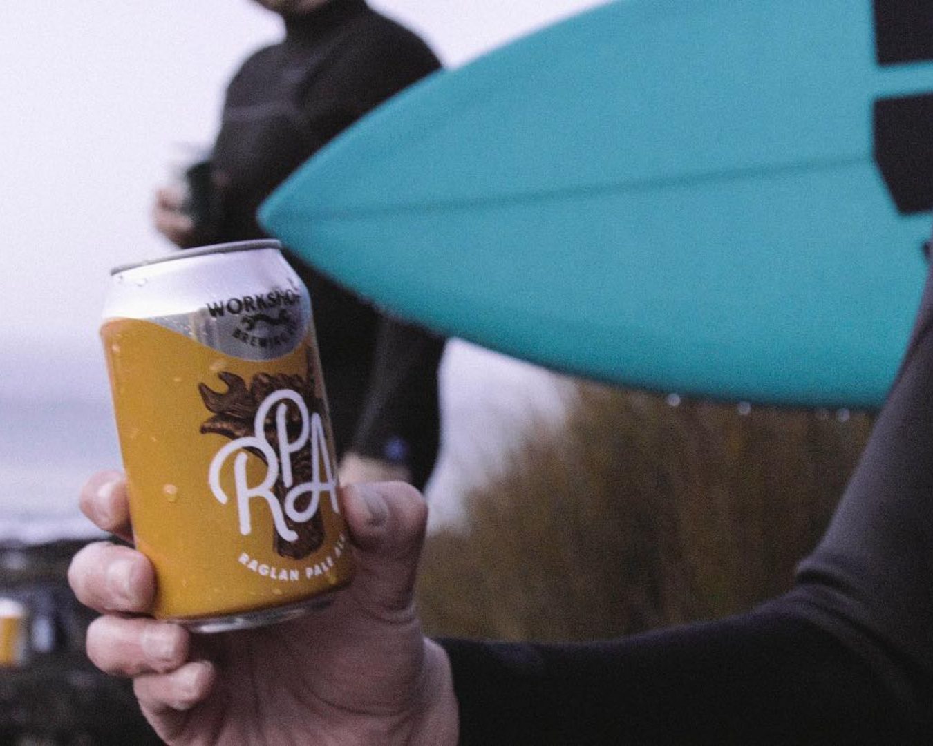 A surfer holding a can of Raglan Pale Ale