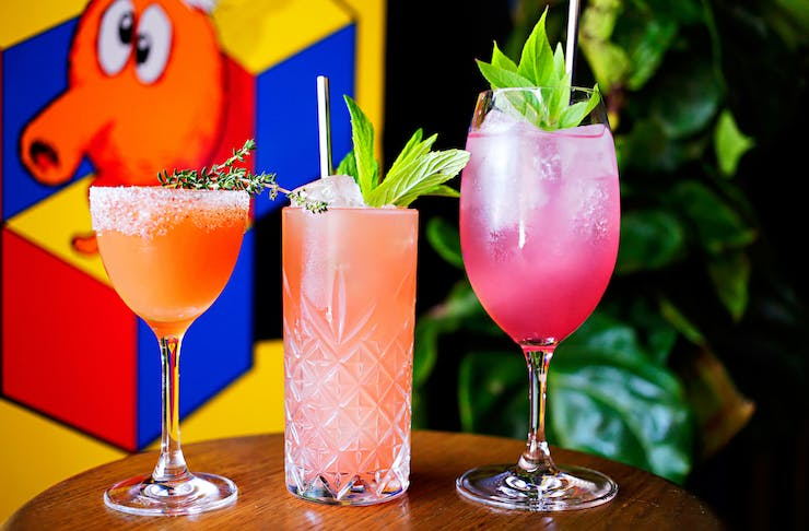 Three colourful cocktails sitting on a bar
