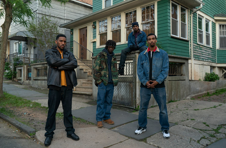 The cast of Wu-Tang: An American Saga standing in front of a green house