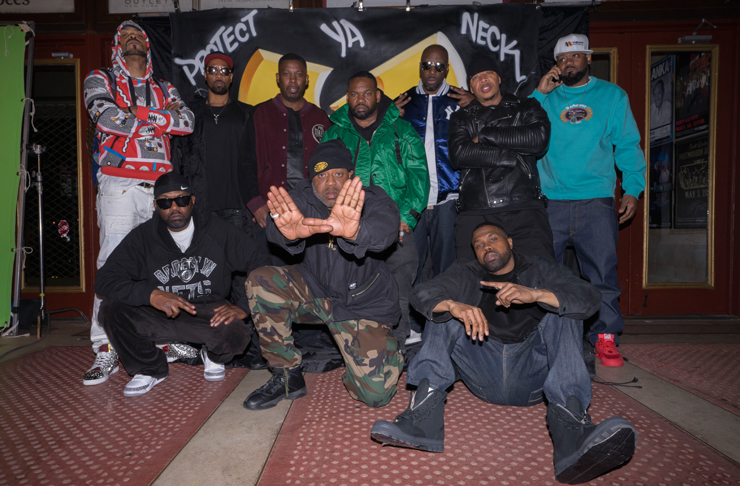 The Wu-Tang Clan posing in front of their famous insignia