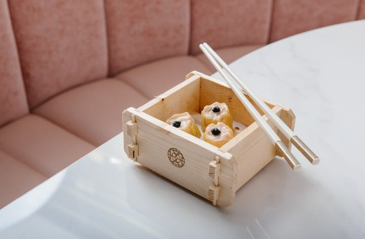 yum cha in wooden box, on marble table, with pink couch in background.