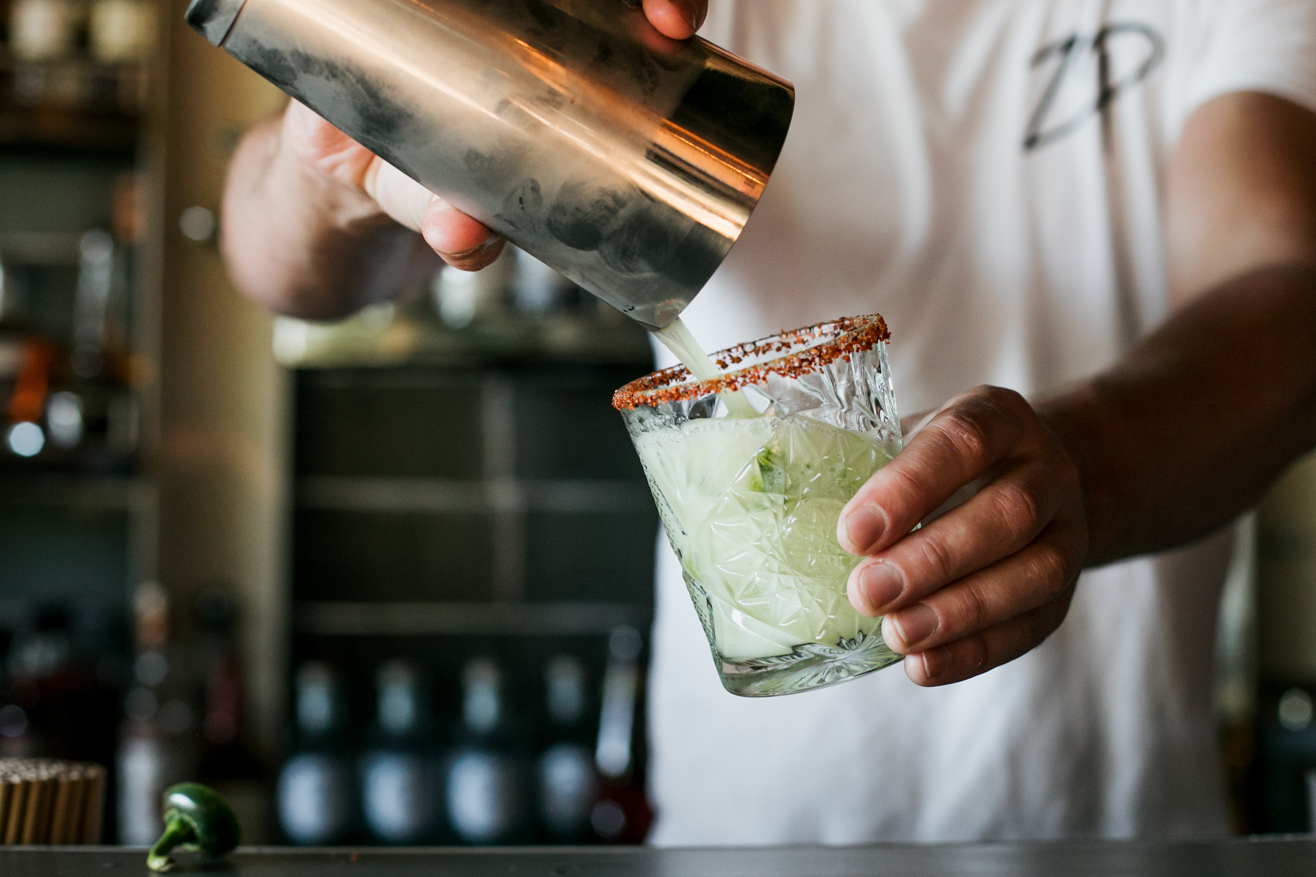 someone pouring a cocktail out of a stainless steel shaker