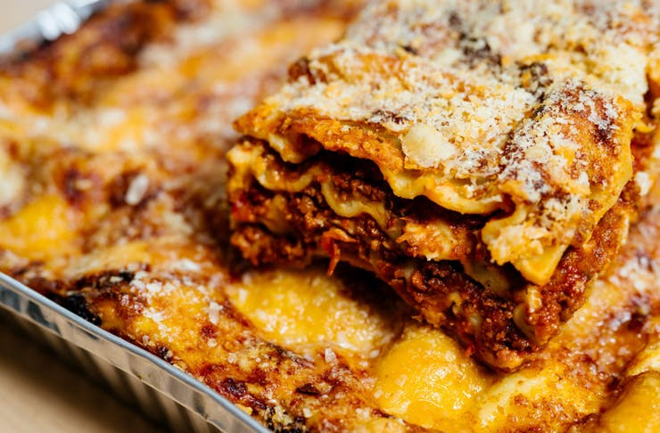 A cheesy, meaty piece of lasagne sitting on top of a tray of takeaway lasagne in Perth